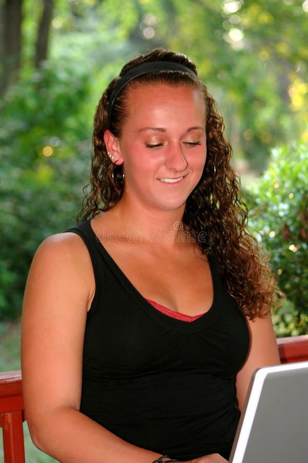 Le den tonåriga flickan som ner ser på bärbara datorn arkivfoton