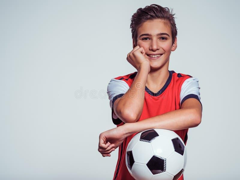 Le den tonåriga pojken i hållande fotbollboll för sportswear arkivbild