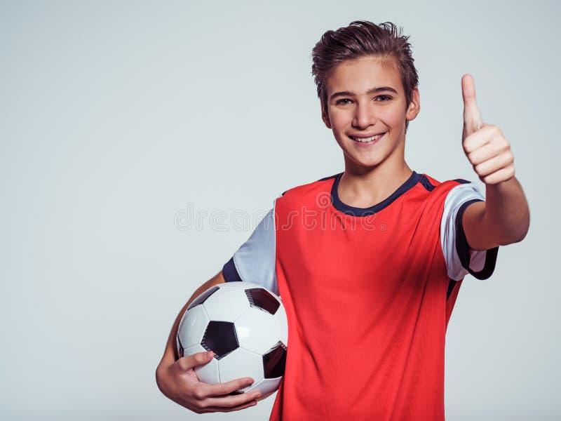 Le den tonåriga pojken i hållande fotbollboll för sportswear royaltyfri bild