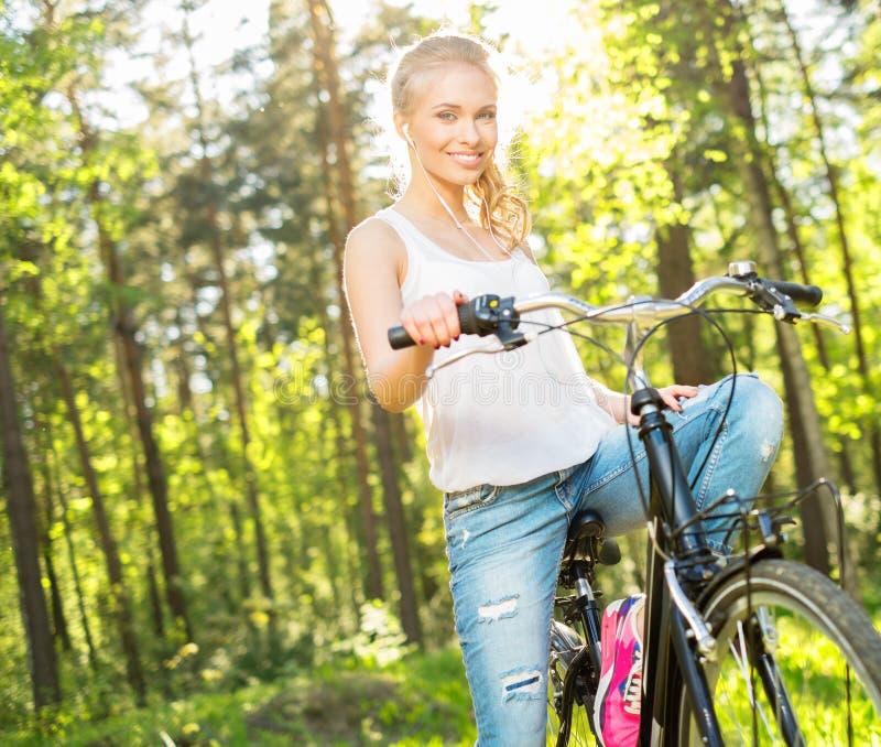 Le den tonårs- flickan med cykeln royaltyfria bilder