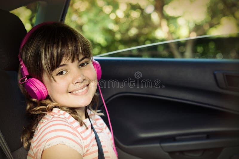 Le den tonårs- flickan med hörlurar i baksätet av bilen arkivfoton