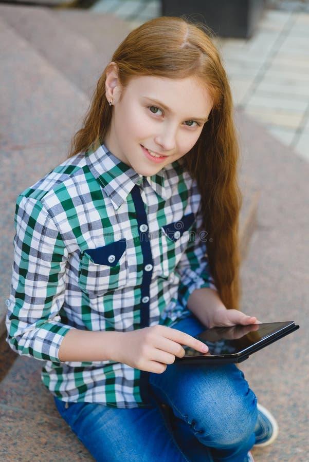 Le den tonårs- flickan med minnestavlaPCdatoren utomhus royaltyfria foton