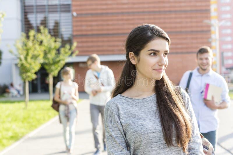 Le den tonårs- flickan som bort ser, medan gå med vänner på universitetsområdet arkivfoto