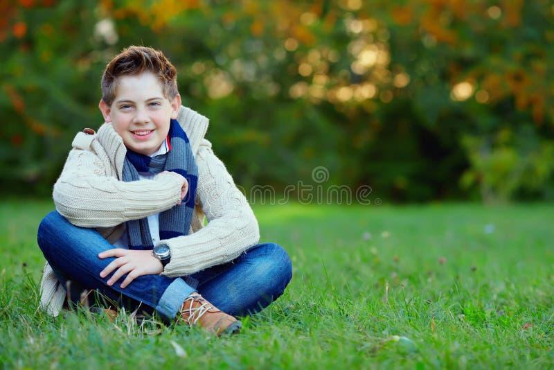 Le den tonårs- pojken på grön gräsmatta royaltyfri foto