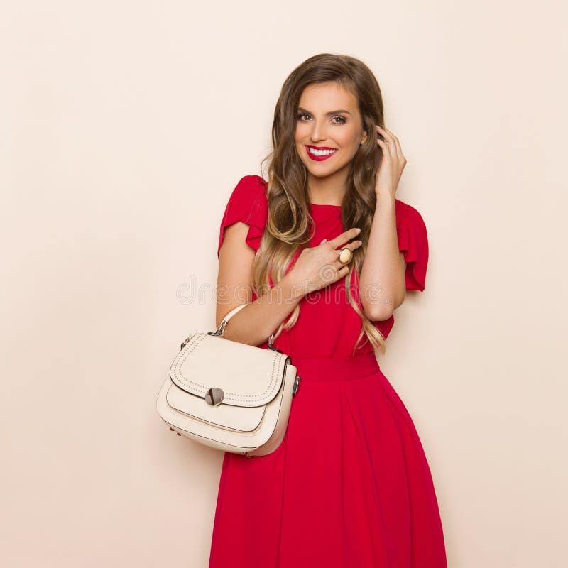 Le den trendiga kvinnan i röd klänning med den beigea handväskan fotografering för bildbyråer
