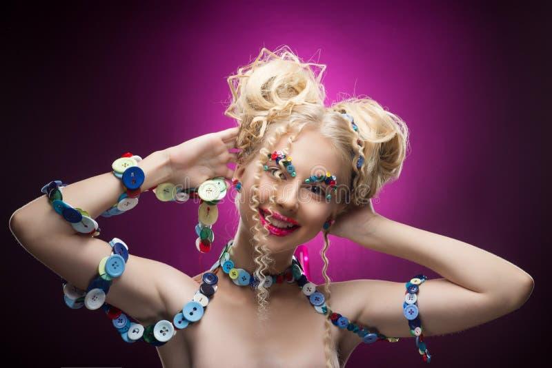 Le den trevliga blonda barnflickan för gullig framsida som bär DIY-smyckeacces royaltyfria bilder