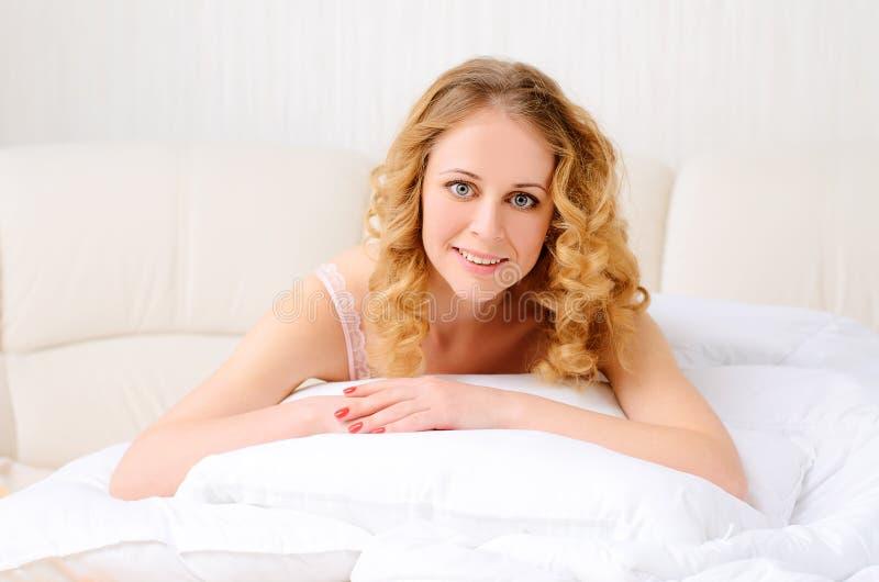 Le den trevliga unga kvinnan på vit säng fotografering för bildbyråer