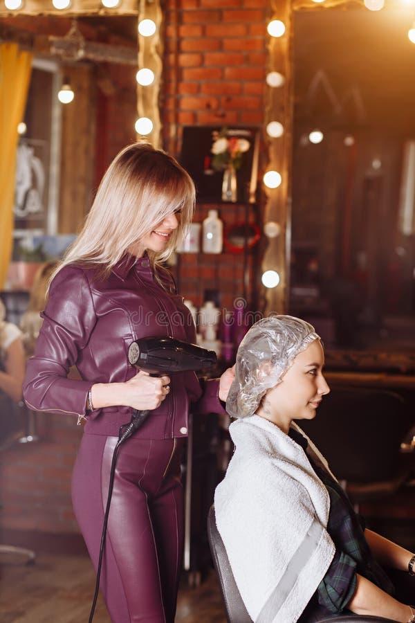 Le den trevliga yrkesmässiga frisören som arbetar med den kvinnliga klienten som rymmer den yrkesmässiga hårtorken i hårsalong Sk royaltyfri bild