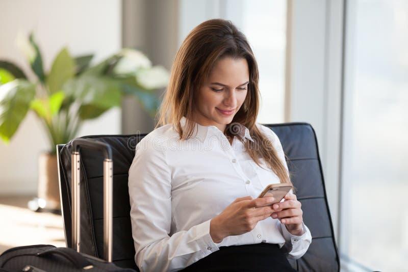 Le den unga affärskvinnan som använder smartphonen, medan vänta med arkivfoto
