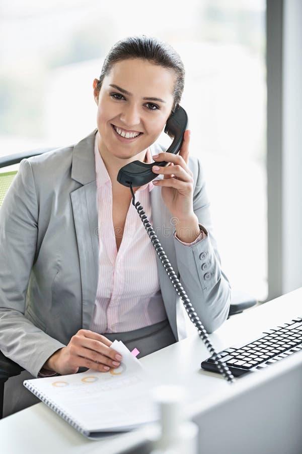 Le den unga affärskvinnan som i regeringsställning talar på telefonen royaltyfri foto