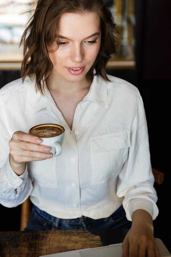 Le den unga affärskvinnan som inomhus sitter på kafét arkivbild