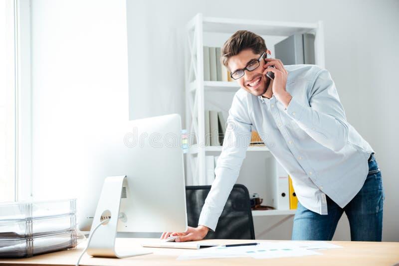 Le den unga affärsmannen genom att använda datoren och tala på mobiltelefonen royaltyfria bilder