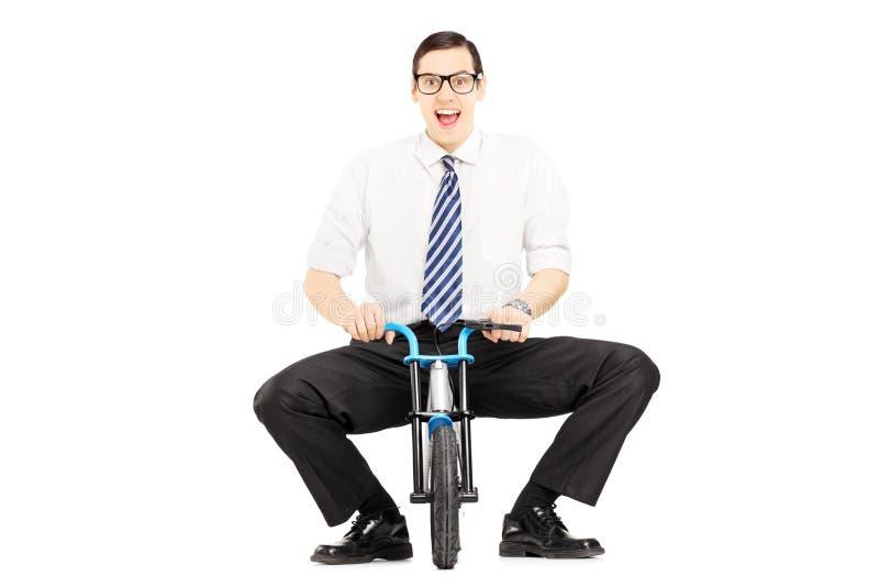 Le den unga affärsmannen som rider en liten cykel royaltyfri fotografi