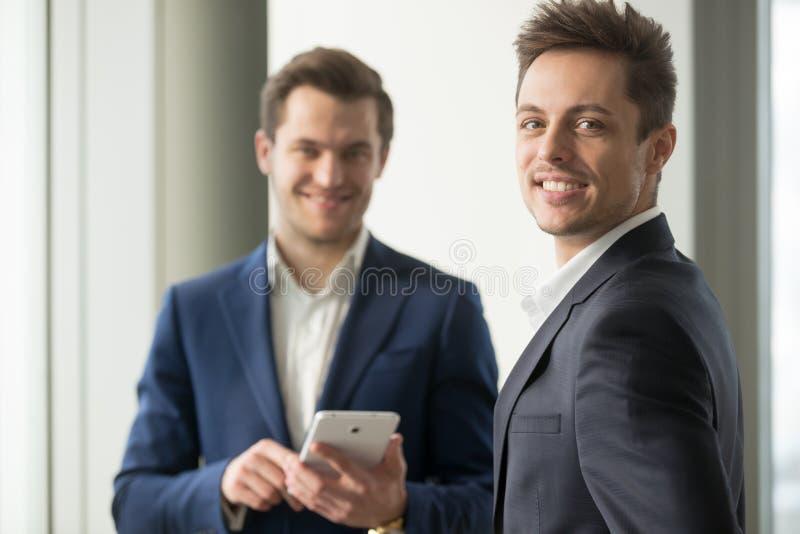 Le den unga affärsmannen som ser kameran, framkallar applikationen arkivfoto