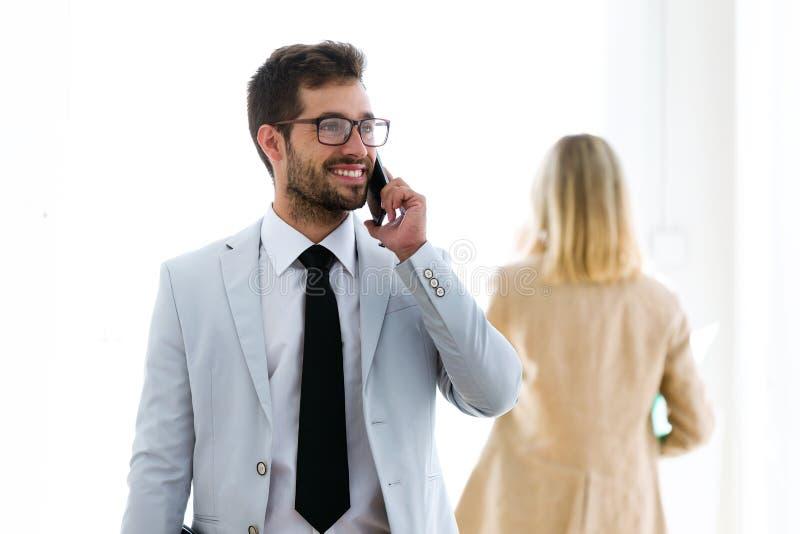 Le den unga affärsmannen som talar med hans smartphones i ett hall av dem företag arkivbild