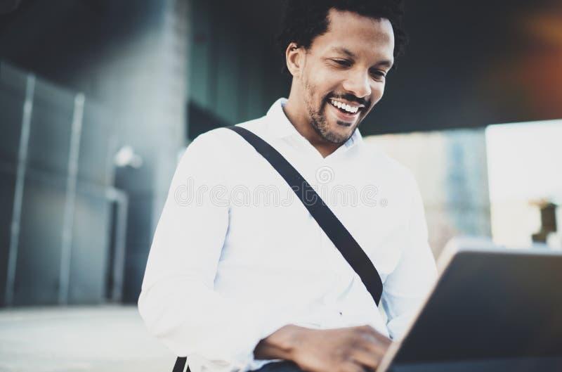 Le den unga afrikanska amerikanen man överföring av emailen via elektroniskt pro-innehav för handlagblock i händer Begrepp av att royaltyfri bild