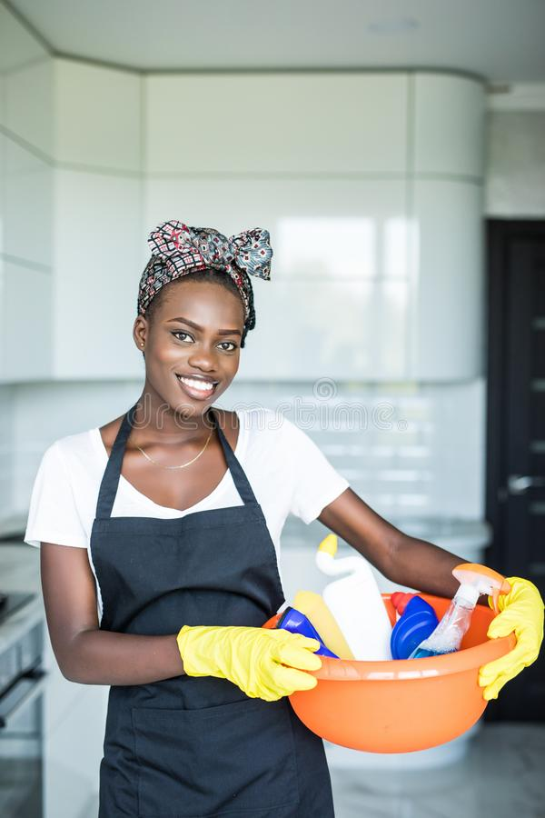 En ung afrikansk kvinna som leker i en korg med rengöringsutrustning på stugan royaltyfria foton