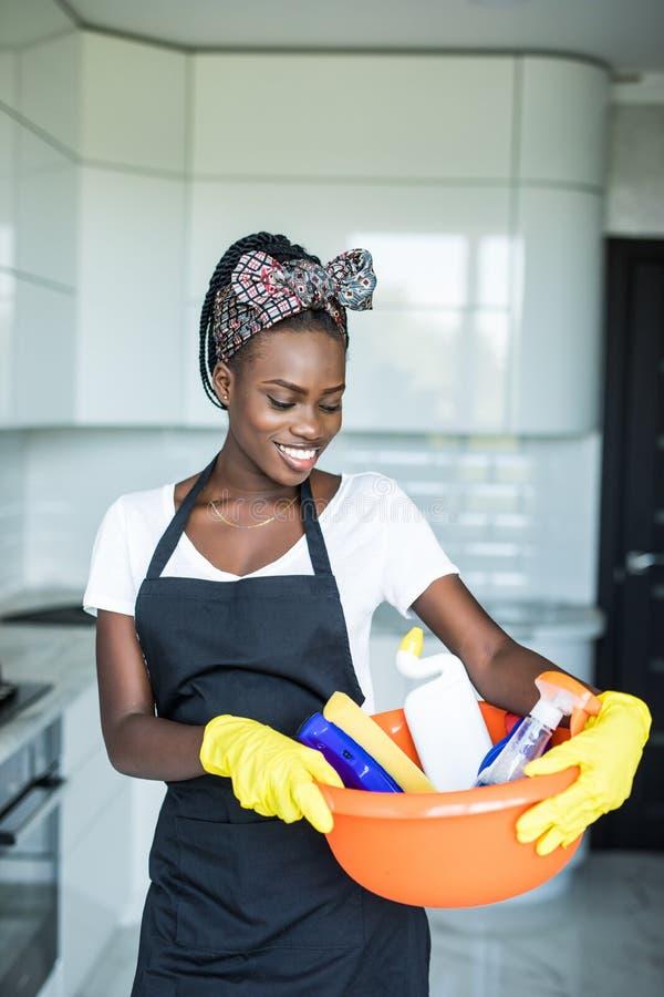 En ung afrikansk kvinna som leker i en korg med rengöringsutrustning på stugan royaltyfri bild