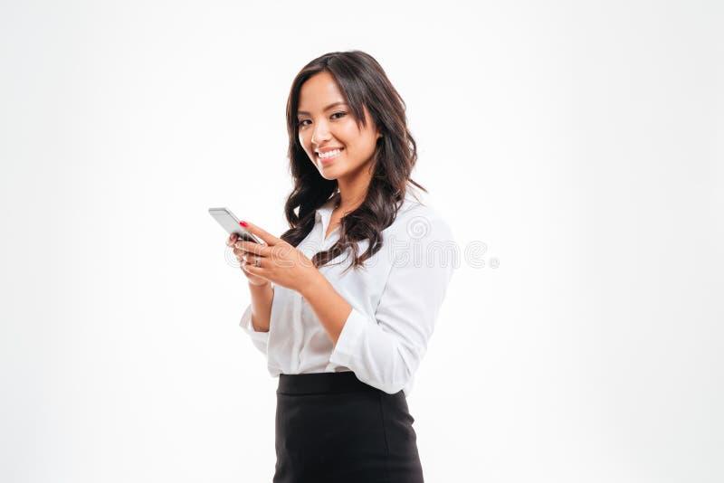 Le den unga asiatiska affärskvinnan som använder smartphonen royaltyfria foton