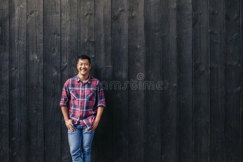 Le den unga asiatiska mannen som utanför lutar mot en mörk vägg royaltyfria bilder