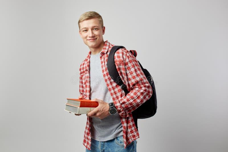 Le den unga blonda grabben med den svarta ryggsäcken på hans iklädda skuldra en vit t-skjorta, en röd rutig skjorta och en jeans arkivfoto