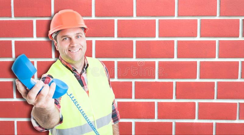 Le den unga byggmästaren som ger telefonen royaltyfri foto