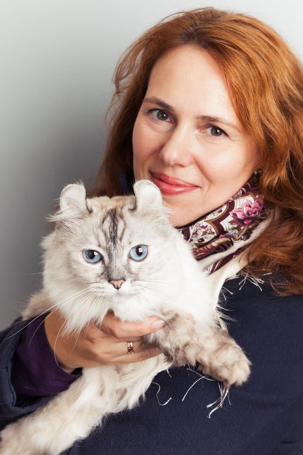 Le den unga Caucasian kvinnan med den vita katten royaltyfri bild