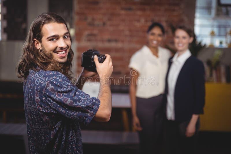 Le den unga fotografen som fotograferar kvinnliga kollegor royaltyfri fotografi