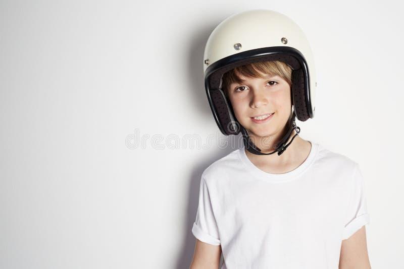 Le den unga gulliga gladlynta tonåriga pojken i den vita tshirten som draming för att rida en motorcykel som isoleras på vit bakg royaltyfri bild