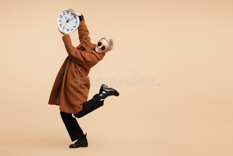 Le den unga hipsterkvinnan med blont kort hår som bär ett lag och solglasögon, dansa med klockan som isoleras över beiga arkivbilder