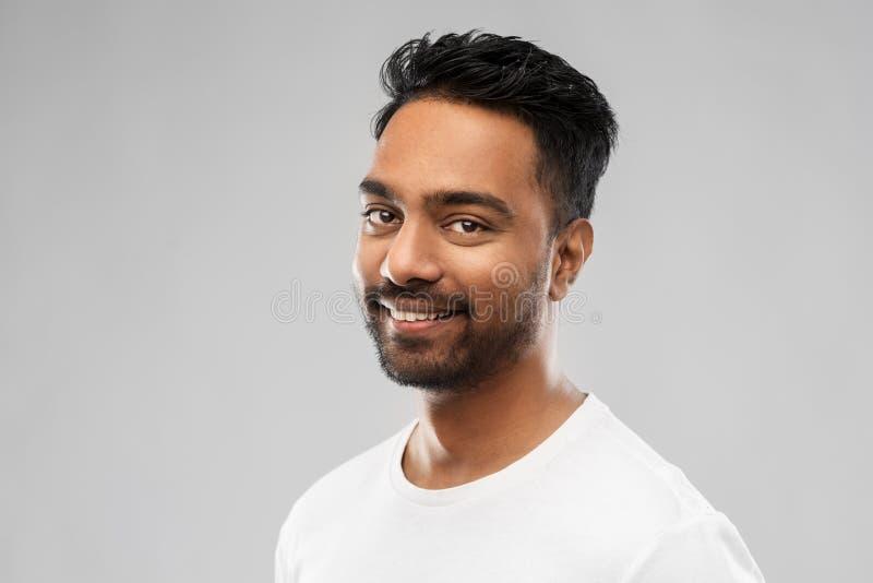 Le den unga indiska mannen över grå bakgrund arkivfoto