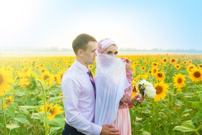 Le den unga islamiska parståenden på solrosfält Muslimsk förbindelse royaltyfri foto