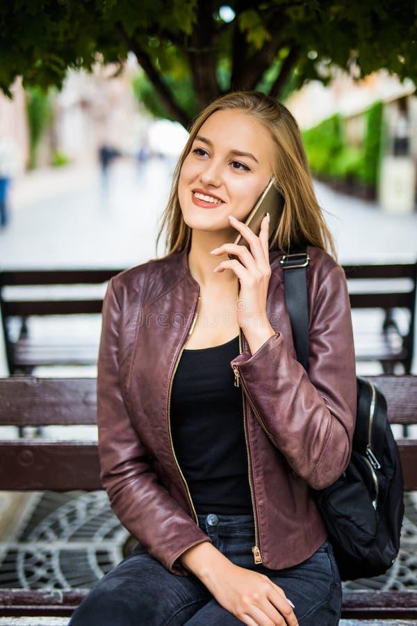 Le den unga kvinnan eller den tonårs- flickan som kallar på smartphonen på stadsgatan royaltyfria bilder