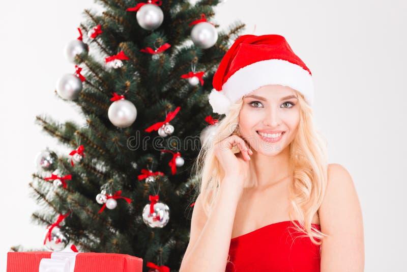 Le den unga kvinnan i den Santa Claus hatten nära julgranen arkivfoto