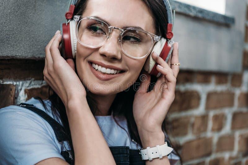 Le den unga kvinnan i glasögon som bär hörlurar och bort ser royaltyfri bild