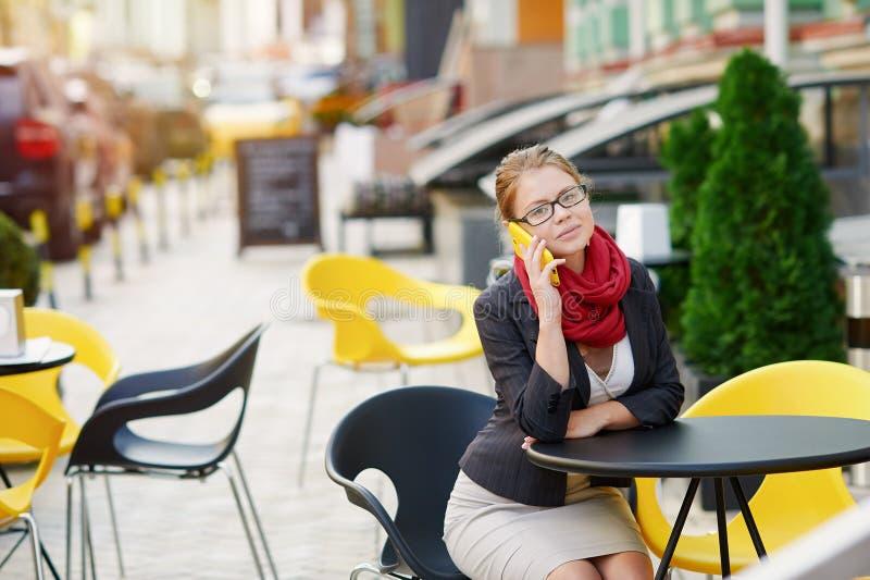 Le den unga kvinnan i glasögon som kallar på smartphonen på kafét royaltyfri bild