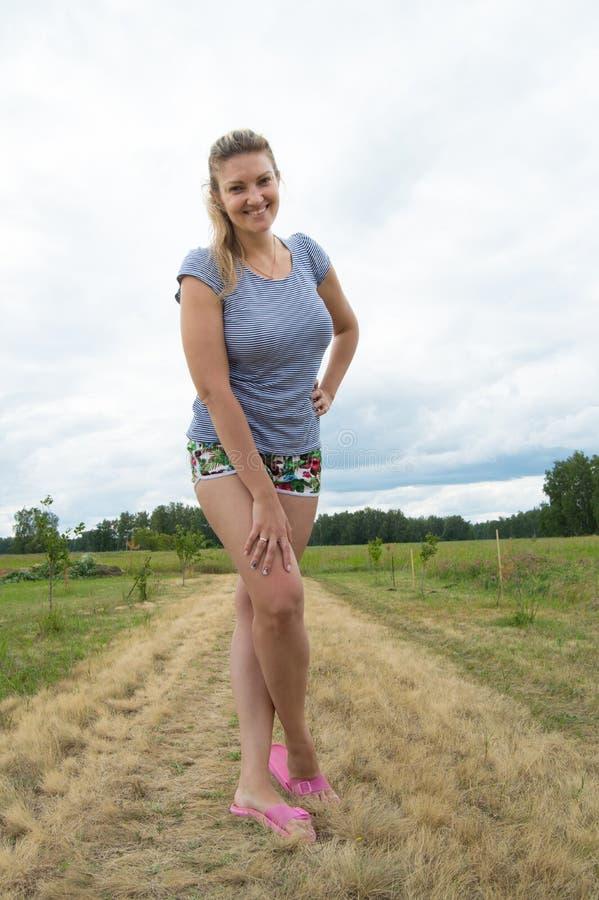 Le den unga kvinnan i kortslutningar och t-skjortan som poserar på en bakgrund av gräs och himmel royaltyfri bild