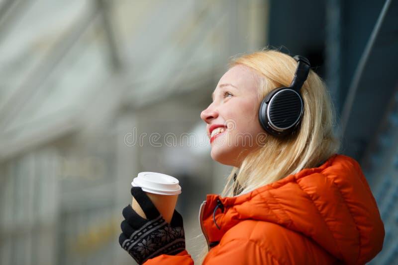 Le den unga kvinnan i vinter klå upp att lyssna till musik I arkivfoton