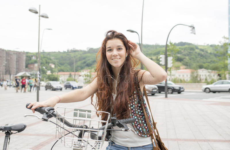 Le den unga kvinnan med cykeln och hörlurar i gatan arkivbild