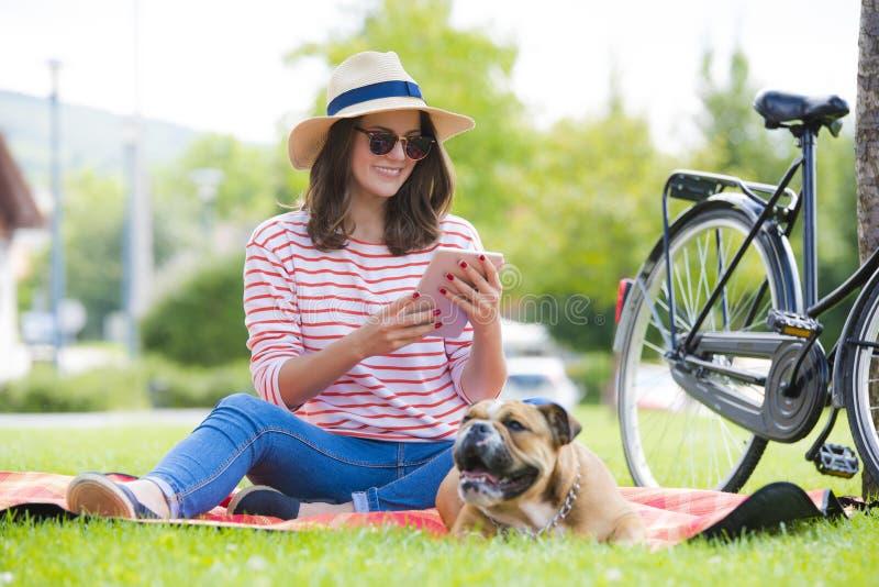 Le den unga kvinnan med den utomhus- digitala minnestavlan royaltyfria foton