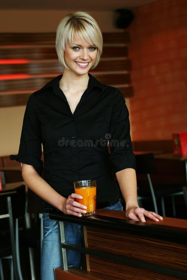 Le den unga kvinnan med ett exponeringsglas av orange fruktsaft royaltyfri fotografi