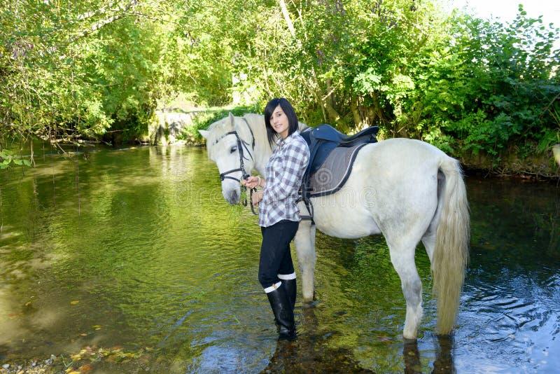 Le den unga kvinnan med hästen i floden royaltyfri fotografi