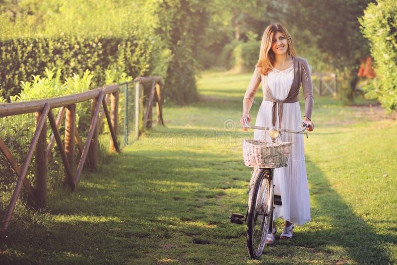 Le den unga kvinnan med hennes gamla cykel arkivbilder