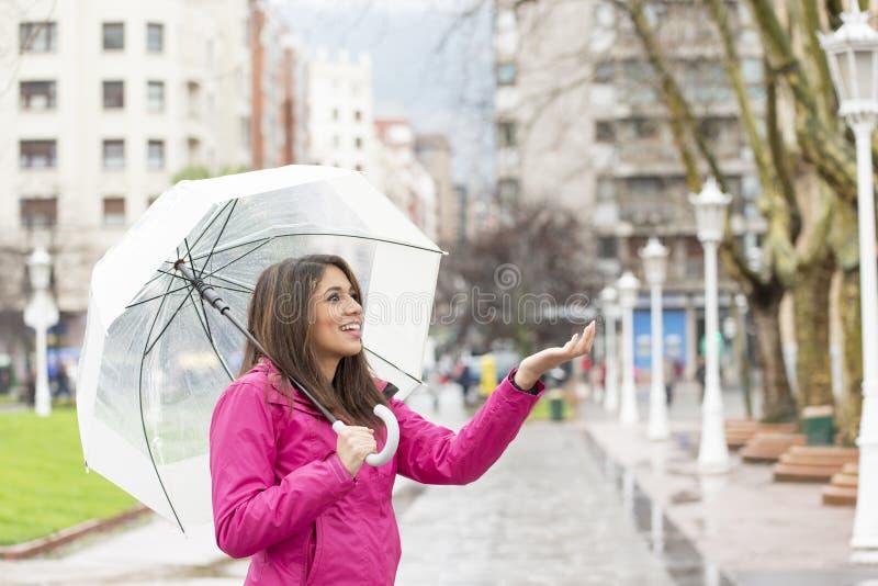 Le den unga kvinnan med paraplyet som kontrollerar för regn arkivfoto