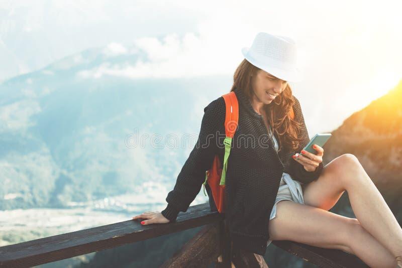 Le den unga kvinnan med ryggsäck- och vithattsammanträde i berg och maskinskrivningmeddelandet på hennes mobiltelefon arkivbild