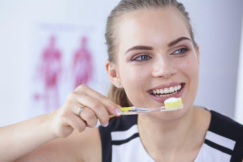 Le den unga kvinnan med sunda tänder som borstar hennes tänder arkivfoton