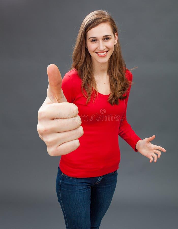 Le den unga kvinnan med tummar upp för symbol av tillfredsställelse arkivbild