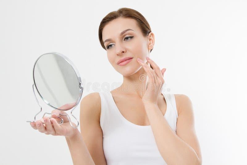Le den unga kvinnan med vita tänder som ser i spegeln som isoleras på vit bakgrund Hudomsorg och anti-åldras begrepp _ arkivfoton