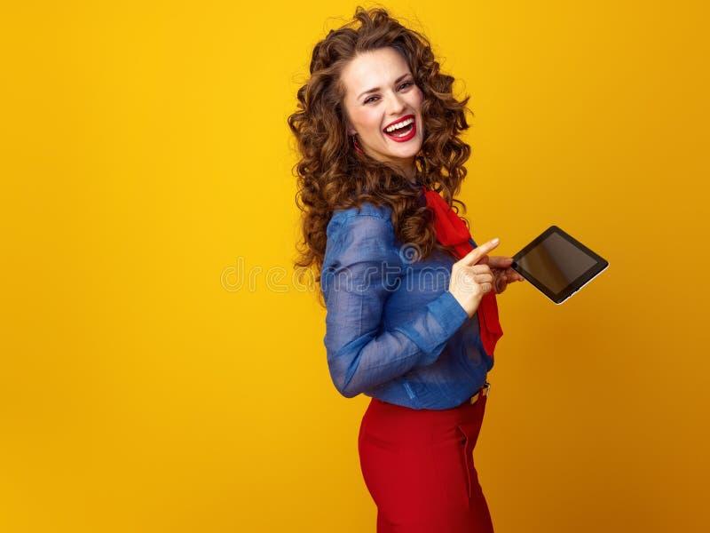 Le den unga kvinnan på gul bakgrund genom att använda minnestavlaPC royaltyfri foto