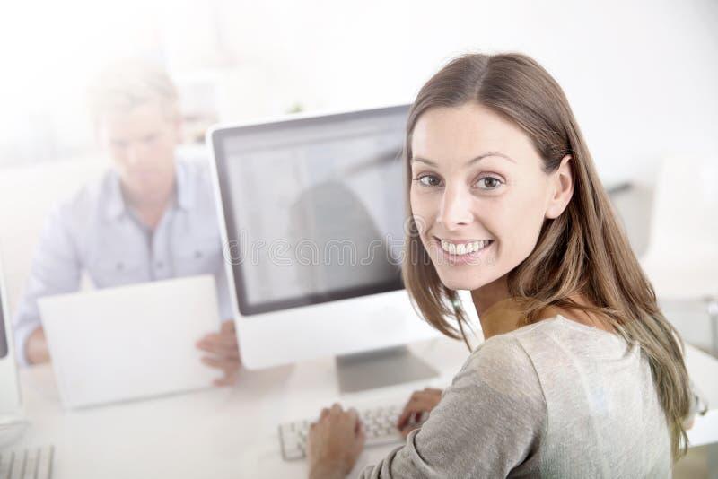 Le den unga kvinnan på kontorsarbete fotografering för bildbyråer